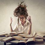 Mujer-con-estrés-y-muchos-libros-en-la-mesa